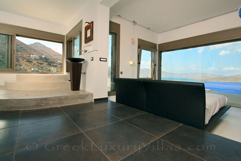 The master bedroom in a modern luxury villa with a pool in Elounda