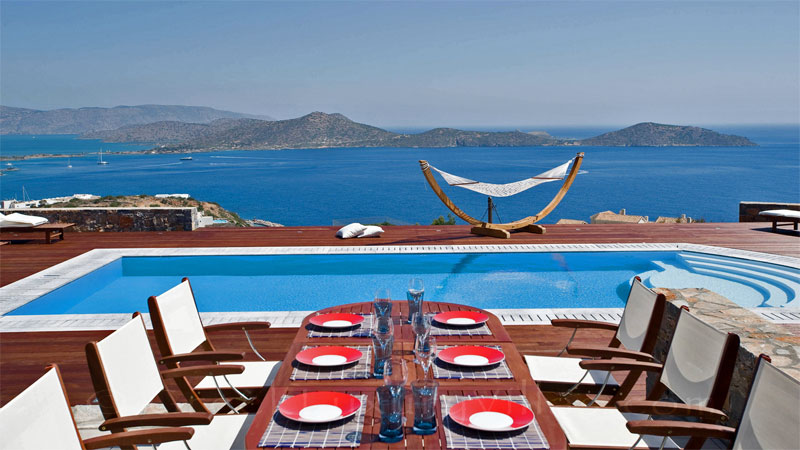 Outdoor dining area of a modern luxury villa overlooking Elounda bay