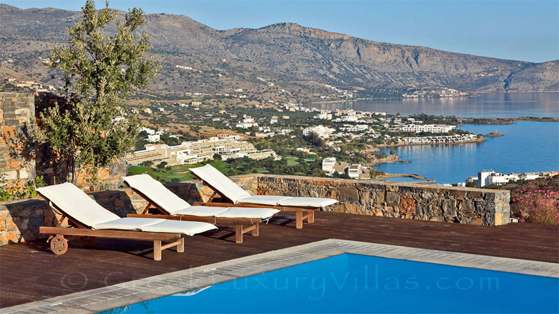 A modern luxury villa with a pool overlooking Elounda bay