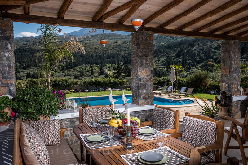 Veranda and outdoor dining area with view to nature in luxury villa with pool in Crete