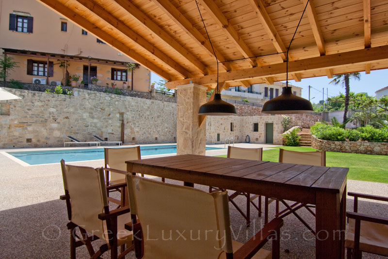 Outdoor dining area of a luxury villa with a pool in a traditional village