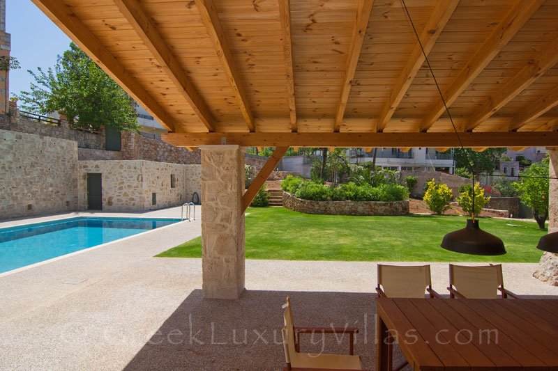 Dining area of a luxury villa with a pool in a traditional village