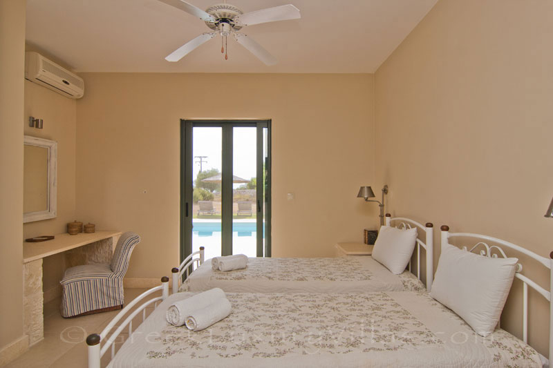 A twin bedroom in a modern villa with a pool in Kefalonia