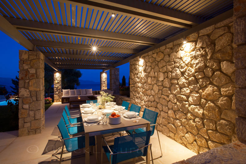Outdoor dining area of a modern luxury villa with a pool in Lefkada