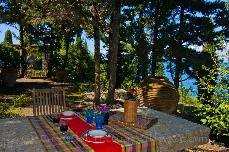 The dining table in the garden of a beachfront villa in Paxos
