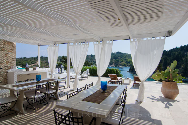The outdoor dining area of a seafront luxury villa in Paxos where groups can dine together