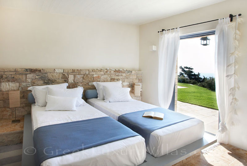 A twin bedroom in a beachfront villa with a pool in Paxos