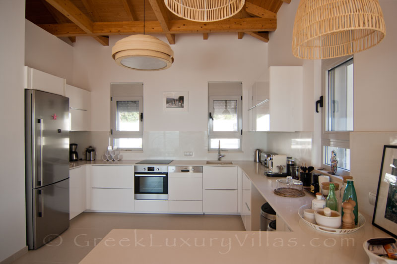 The kitchen of a modern luxury villa with a pool in Paxos