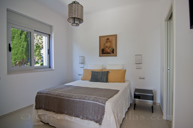 A bedroom in a modern luxury villa with a pool in Paxos