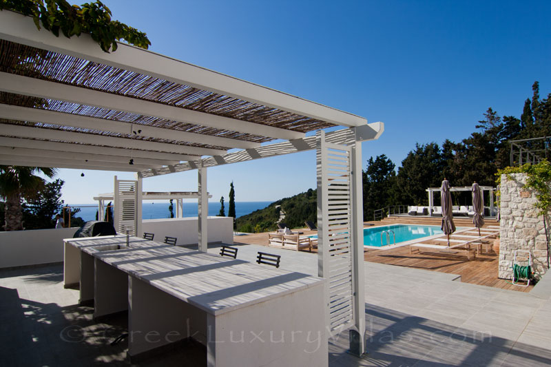The pool bar of a modern luxury villa with a pool and seaview in Paxos