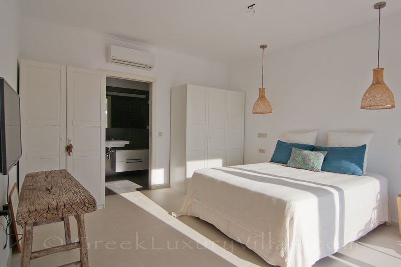 A bedroom in the guest house of a modern luxury villa with a pool in Paxos