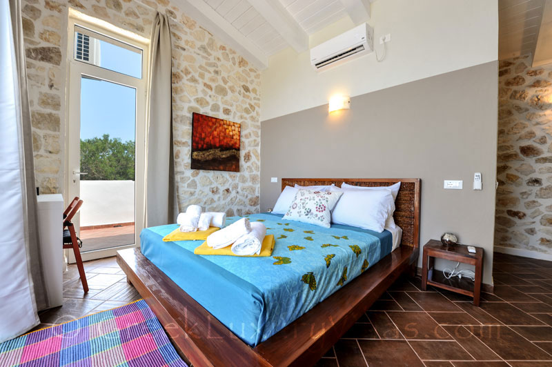 A bedroom of a cheerfully decorated villa with a pool and seaview in Paxos