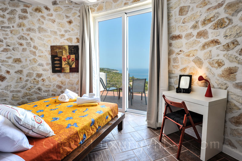 The bedroom of a villa with a pool and seaview in Paxos