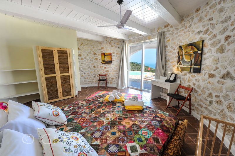 A cheerful bedroom with sea view in a villa with a pool in Paxos