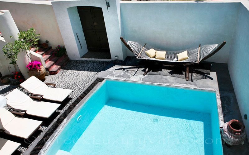 A traditional village in Santorini with a luxurious villa with a pool