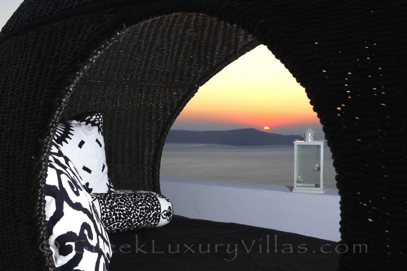 Sunset view from the rooftop jacuzzi of a luxury villa in Fira, Santorini