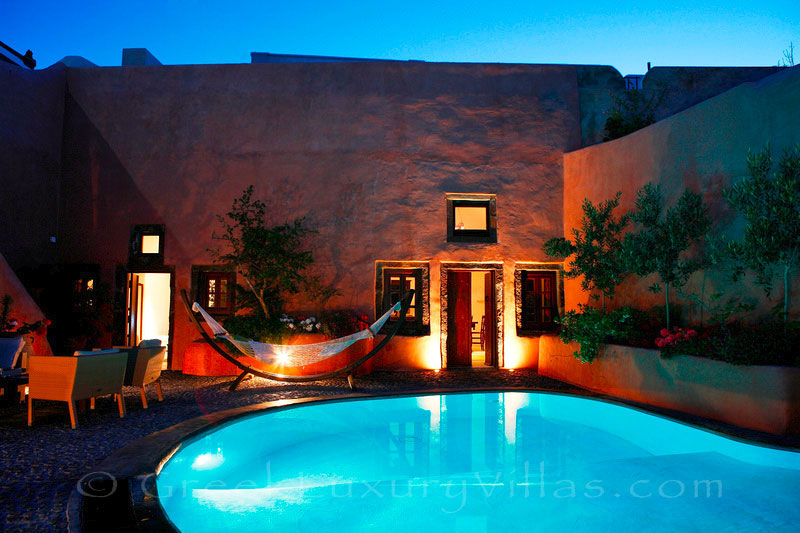 A traditional village house with a pool in Santorini at night