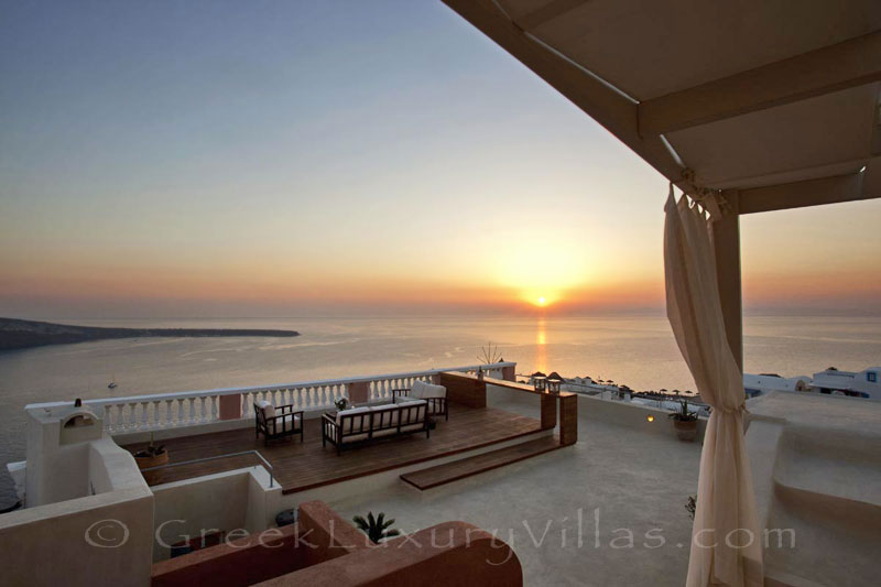 Panoramic sunset view from the roof terrace of a luxury villa in Oia, Santorini