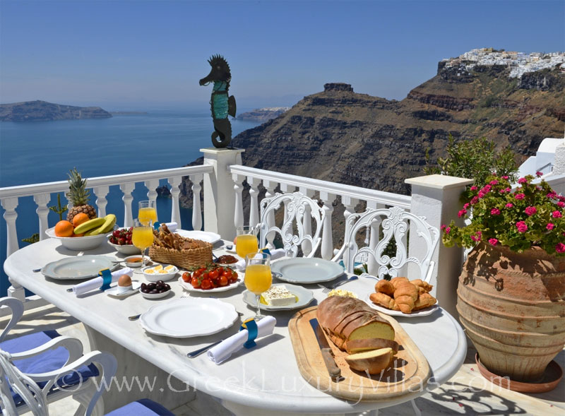 Breakfast with seaview in a large villa with a pool on the cliff in Santorini
