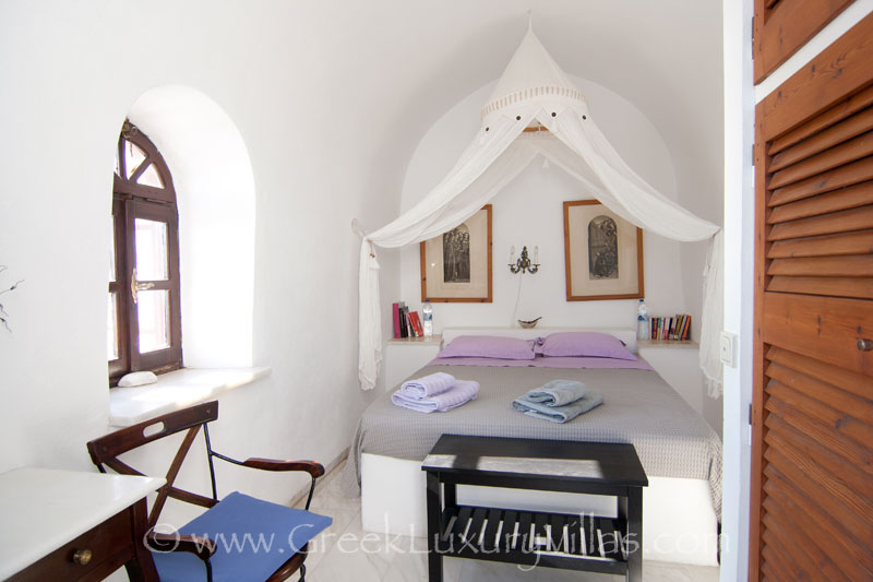 A bedroom with a chapel in large villa with a pool on the cliff in Santorini