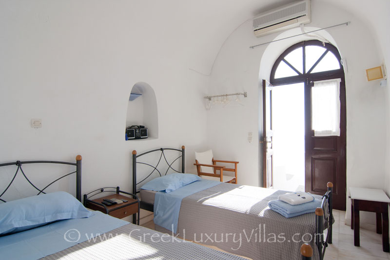A twin bedroom in a large villa with a pool on the cliff in Santorini