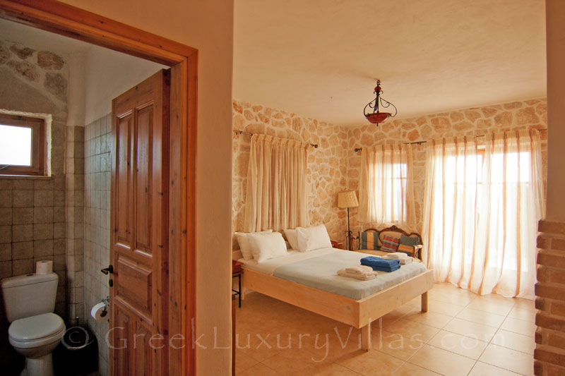 A bedroom of the villa with seaview and a pool