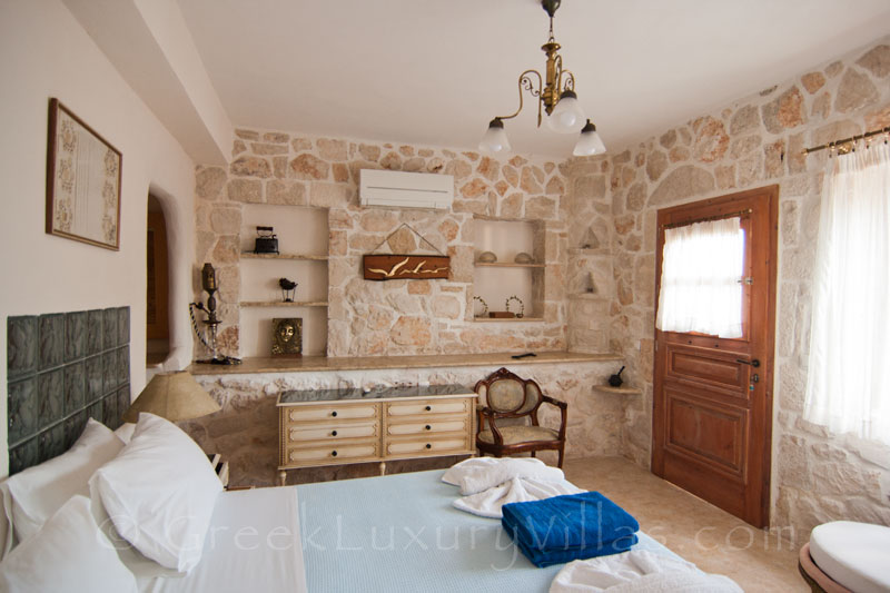The bedroom of a villa with seaview and a pool